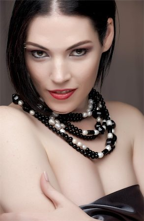 Sexy naked young caucasian adult woman with red lips, short black hair and a pierced eyebrow, covered in a dark satin sheet and wearing a black and white pearl string necklace Stock Photo - Budget Royalty-Free & Subscription, Code: 400-04802257