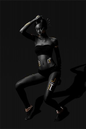 Beautiful exotic African female fashion with tribal yellow red and white cultural makeup cosmetics and sticks in hair, in cultural dance position. Stock Photo - Budget Royalty-Free & Subscription, Code: 400-04803745