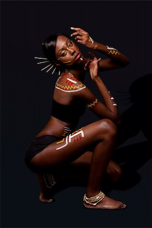 Beautiful exotic African female fashion with tribal yellow red and white makeup cosmetics and sticks in hair, in cultural dance position. Stock Photo - Budget Royalty-Free & Subscription, Code: 400-04803750