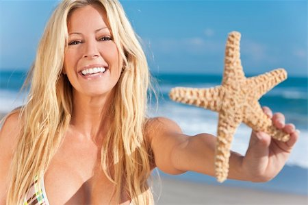 simsearch:400-04002563,k - A beautiful young blond woman holding a starfish wearing a bikini on a beach and laughing Stock Photo - Budget Royalty-Free & Subscription, Code: 400-04814150