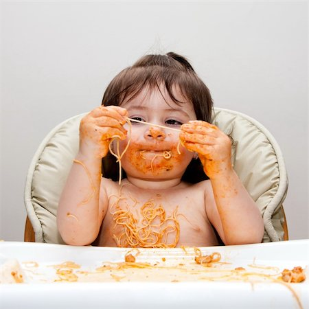 Happy baby having fun eating messy covered in Spaghetti holding Angel Hair Pasta red marinara tomato sauce. Stock Photo - Budget Royalty-Free & Subscription, Code: 400-04844562