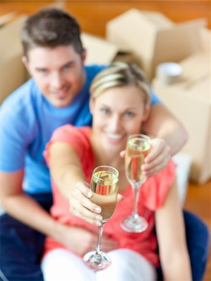 Young couple sitting on the floor in flat celebrating removal with champagne. Stock Photo - Royalty-Free, Artist: 4774344sean, Image code: 400-04841277