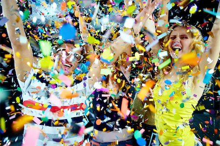 Photo of excited teenagers in confetti raising their arms expressing joy Stock Photo - Budget Royalty-Free & Subscription, Code: 400-04864286
