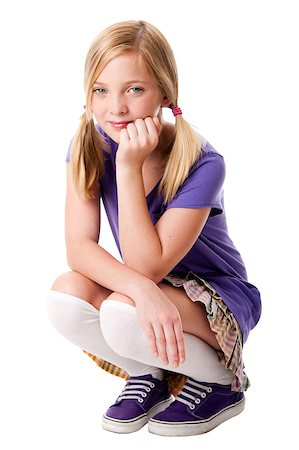 Beautiful happy teenage girl sitting squatted wearing knee socks, puple sporty shoes, shirt and colorful skirt, hand supporting her head, isolated. Stock Photo - Budget Royalty-Free & Subscription, Code: 400-04885417