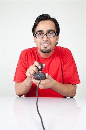 nerd looking young guy playing his favoriteold video game. Stock Photo - Budget Royalty-Free & Subscription, Code: 400-04887558