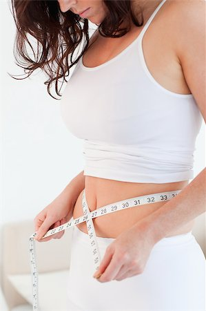 Good looking brunette woman measuring her belly with a tape measure while standing in her bedroom Stock Photo - Budget Royalty-Free & Subscription, Code: 400-04882155