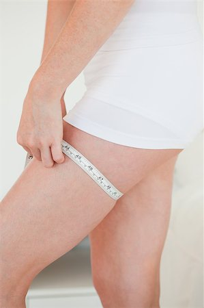 Woman measuring her hip with a tape measure while standing in her bedroom Stock Photo - Budget Royalty-Free & Subscription, Code: 400-04882161