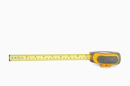 Yellow measuring tape partly unrolled against a white background Stock Photo - Budget Royalty-Free & Subscription, Code: 400-04882301
