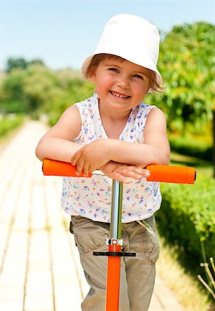 raysay (artist) - Little adorable girl posing with orange scooter in the park Stock Photo - Budget Royalty-Free & Subscription, Code: 400-04893845