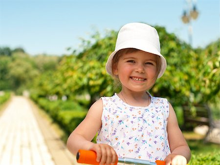 raysay (artist) - Little adorable girl posing with orange scooter in the park Stock Photo - Budget Royalty-Free & Subscription, Code: 400-04893848