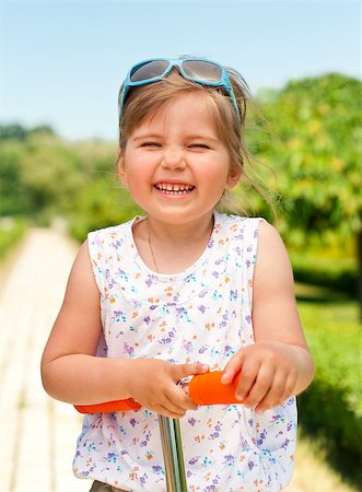raysay (artist) - Little adorable girl posing with orange scooter in the park Stock Photo - Budget Royalty-Free & Subscription, Code: 400-04893849