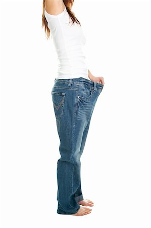 Slim woman pulling oversized jeans. Weight loss concept. Isolated on white Stock Photo - Budget Royalty-Free & Subscription, Code: 400-04915794
