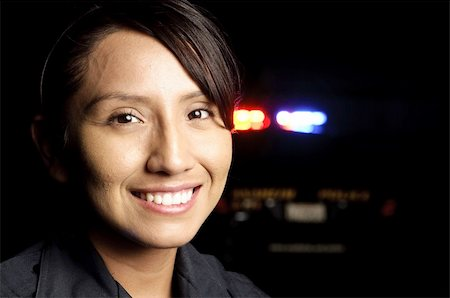 female police officer happy - a smiling police officer with her patrol unit in the background with its lights on. Stock Photo - Budget Royalty-Free & Subscription, Code: 400-04917195