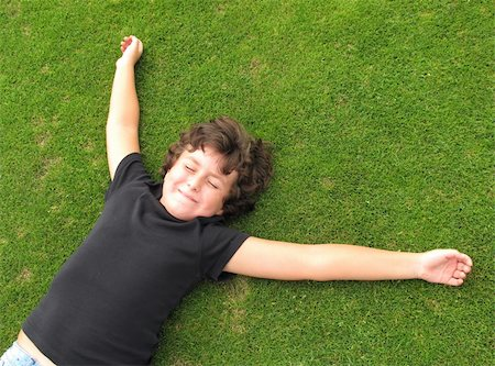 Happy child resting on a beautiful green grass Stock Photo - Budget Royalty-Free & Subscription, Code: 400-04917677