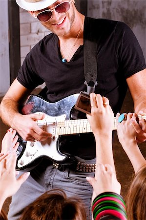 Rock guitarist playing in front of a cheering crowd. Stock Photo - Budget Royalty-Free & Subscription, Code: 400-04924488