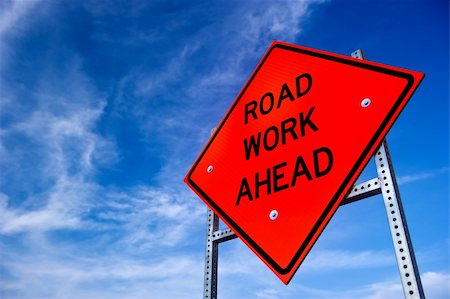 Image of a bright orange road work ahead sign against a blue sky with light clouds Stock Photo - Budget Royalty-Free & Subscription, Code: 400-04925891
