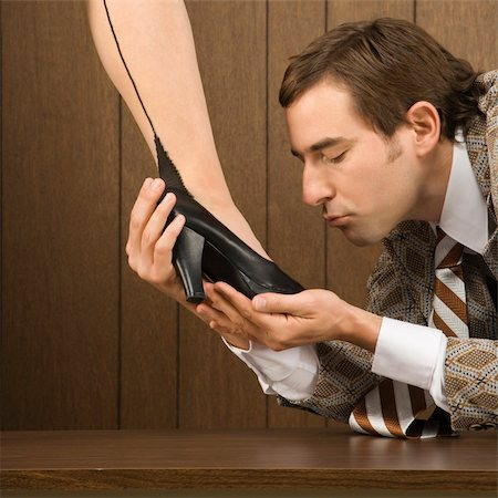 Mid-adult Caucasian male holding Caucasian female shoe and preparing to kiss it. Stock Photo - Budget Royalty-Free & Subscription, Code: 400-04954799