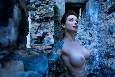 Blue-toned portrait of tattooed sexy nude Caucasian woman next to concrete wall. Stock Photo - Budget Royalty-Free & Subscription, Code: 400-04955721