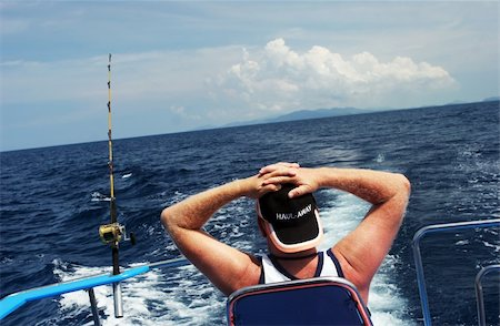 simsearch:400-04638538,k - Man on a boat deep sea fishing is relaxing and waiting for the fish to come. Stock Photo - Budget Royalty-Free & Subscription, Code: 400-04978819