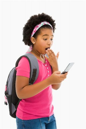 African American girl with backpack looking at cell phone with surprised expression. Stock Photo - Budget Royalty-Free & Subscription, Code: 400-05012508