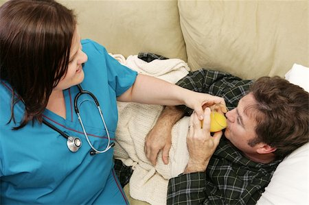 A home health nurse helping her patient drink orange juice.  Focus on him. Stock Photo - Budget Royalty-Free & Subscription, Code: 400-05022193