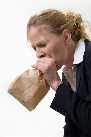 Blond woman holding a brown paper bag over mouth with a distraught expression as if having a panic attack or being nauseated Stock Photo - Budget Royalty-Free & Subscription, Code: 400-05037649
