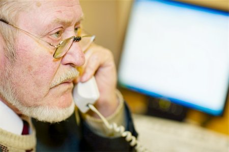 Mature businessman talking on the phone, checking out a document on his computer monitor. Stock Photo - Budget Royalty-Free & Subscription, Code: 400-05030693