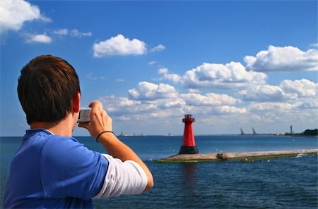 man with a compact camera taking a photo of a lighthouse Stock Photo - Budget Royalty-Free & Subscription, Code: 400-05032734