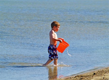 young boy at the beach carrying a bucket with water Stock Photo - Budget Royalty-Free & Subscription, Code: 400-05044017