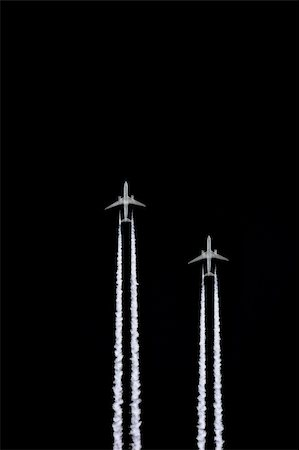 Two jet aircraft flying in a vertical parallel formation with smoke trails, set against a black sky background. Stock Photo - Budget Royalty-Free & Subscription, Code: 400-05045845