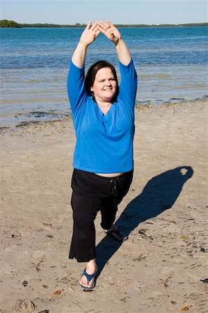 Plus sized model stretching for fitness on the beach.  Vertical view. Stock Photo - Budget Royalty-Free & Subscription, Code: 400-05043078