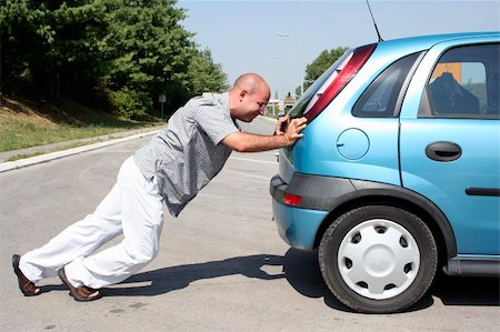 Man pushing a broken car or a car out of gas Stock Photo - Budget Royalty-Free & Subscription, Code: 400-05068357