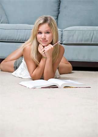 A young girl laying on the floor doing her homework with copyspace on the bottom. Stock Photo - Budget Royalty-Free & Subscription, Code: 400-05074502