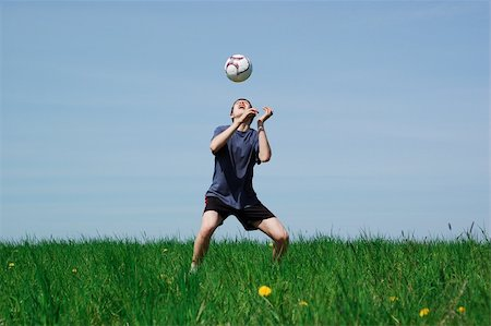 happy boy playing football on sky background Stock Photo - Budget Royalty-Free & Subscription, Code: 400-05075057