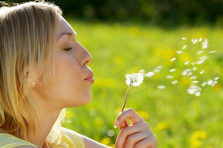 The girl blows on a dandelion on a background of a grass Stock Photo - Budget Royalty-Free & Subscription, Code: 400-05076031