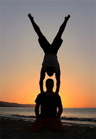 feet gymnast - Two men silhouettes at sunset on the beach Stock Photo - Budget Royalty-Free & Subscription, Code: 400-05082916