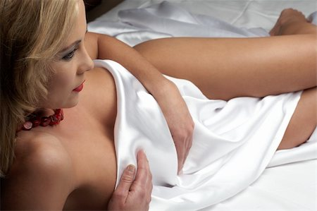 Sensual naked young blonde adult Caucasian woman, wrapped in a satin, silk sheet on a bed in her bedroom. High contrast lighting. Stock Photo - Budget Royalty-Free & Subscription, Code: 400-05083138