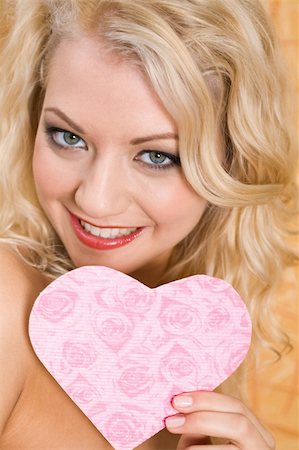 Portrait of glamorous girl holding pink paper heart in hand and smiling Stock Photo - Budget Royalty-Free & Subscription, Code: 400-05090599