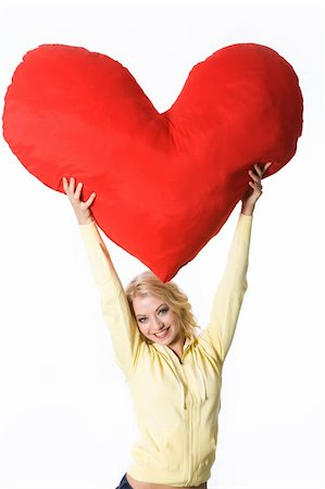 Image of cheerful blonde with big heart-shaped soft toy giving it to you Stock Photo - Budget Royalty-Free & Subscription, Code: 400-05090602
