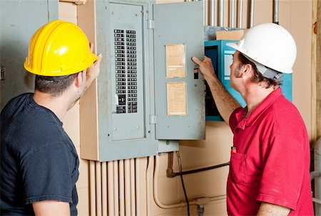 electrician fixing fuse box stock photos page 1 masterfile electrician fixing fuse box electricians examining a circuit breaker panel in an industrial setting