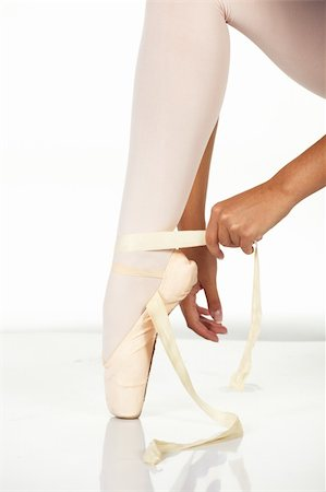 Young female ballet dancer showing how to tie a ballet Pointe Shoe against a white background. NOT ISOLATED Stock Photo - Budget Royalty-Free & Subscription, Code: 400-05138826