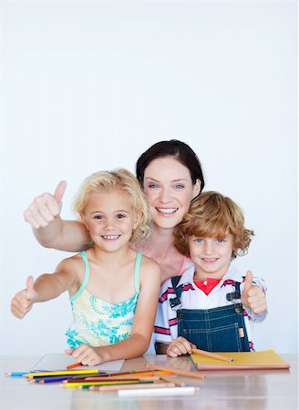 Happy children doing homework with their mother with copy-space Stock Photo - Budget Royalty-Free & Subscription, Code: 400-05145024