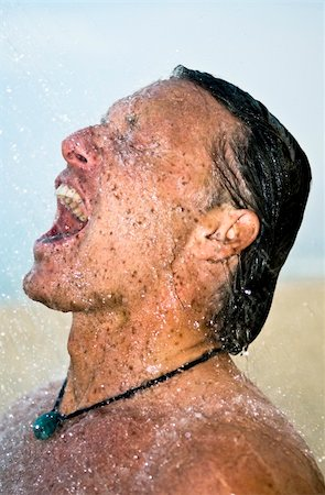A handsome forties man is taking a wash under a powerful shower at the beach. Stock Photo - Budget Royalty-Free & Subscription, Code: 400-05149577