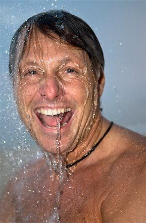 handsome forties man is laughing as he has fun under a powerful shower. Stock Photo - Budget Royalty-Free & Subscription, Code: 400-05149579