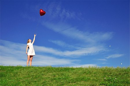 flying heart girl - girl with a red ball in the form of heart on the background of the sky Stock Photo - Budget Royalty-Free & Subscription, Code: 400-05161011