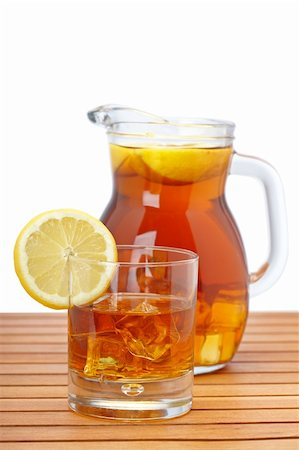 Ice tea pitcher and glasss with lemon and icecubes on wooden background. Focus at front and shallow depth of field Stock Photo - Budget Royalty-Free & Subscription, Code: 400-05174227