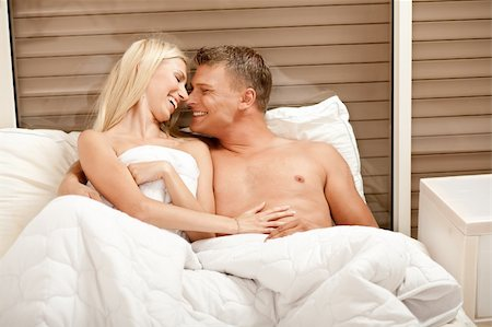 Caucasian couple embracing and enjioying in bed Stock Photo - Budget Royalty-Free & Subscription, Code: 400-05174671
