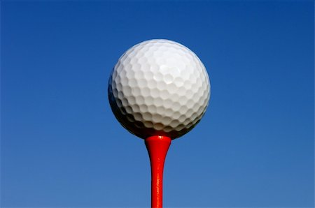 Image of a white golf ball sitting on a red tee Stock Photo - Budget Royalty-Free & Subscription, Code: 400-05192331