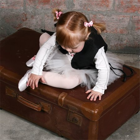 Tiny travelling ballerina sitting on a suitcase wearing a leather undercoat over her tutu Stock Photo - Budget Royalty-Free & Subscription, Code: 400-05210413