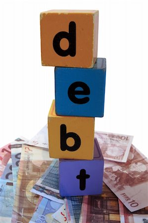 assorted childrens toy letter building blocks against a white background on money that spell debt Stock Photo - Budget Royalty-Free & Subscription, Code: 400-05241315